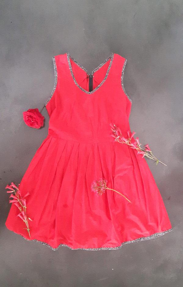 Robe style année 50 esprit rockabilly rouge posée par terre avec des fleurs