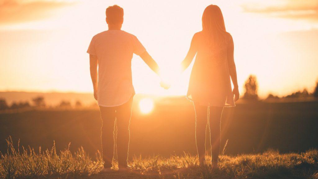 couple qui se tient face à un coucher de soleil