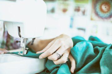 main tenant un tissu vert sur une machine à coudre