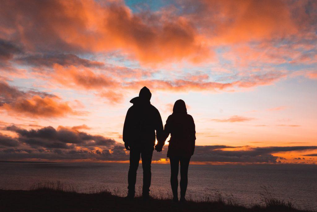 couple regardant au loin un coucher de soleil