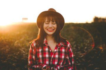 jeune fille brune qui ris portant une chemise rouge à carreaux